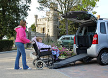 Patient mobility transport for disabled. Photo of a daughter caring for her disabled mother by assisting her into the back of a wheelchair access vehicle after Royalty Free Stock Photos
