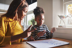 Patient mom teaching daughter schoolwork. At home, black family Royalty Free Stock Image
