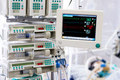 Patient with monitor and infusion pumps in an ICU Royalty Free Stock Photos