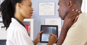 Patient with neck pain talking to doctor about x ray on tablet Royalty Free Stock Photography