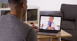 Patient noir discutant des problèmes de santé avec le docteur en ligne Photos libres de droits