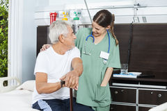 Patient And Nurse Looking At Each Other In Rehab Center. Happy senior male patient and female nurse looking at each other in rehab center Stock Photo