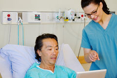 Patient and nurse looking at tablet Stock Photo