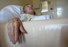Patient in nursing home bed. Photo of a female patient lying in a nursing home bed with her hand hanging down over bed Royalty Free Stock Images
