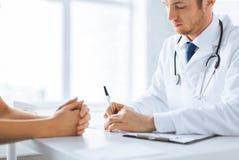 Patient och doktor som tar anmärkningar royaltyfri fotografi