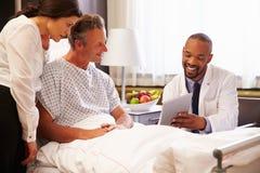 Patient och fru för doktor Talking To Male i sjukhussäng arkivfoto
