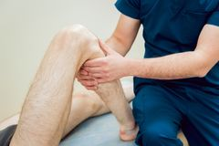 Patient with orthopedist doctor in his office. Royalty Free Stock Image