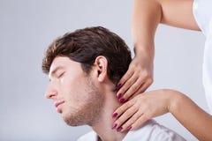 Patient palpationing de physiothérapeute avec le cou raide images stock