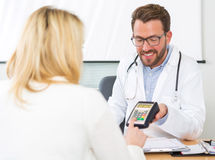 Patient paying the doctor by credit card Royalty Free Stock Photo