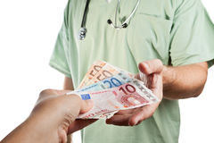 Patient paying to the doctor. Stock Photos