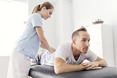 Patient at the physiotherapy doing physical exercises with his therapist. A Patient at the physiotherapy doing physical exercises with his therapist stock photo