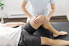 Patient at the physiotherapy doing physical exercises with his therapist. A Patient at the physiotherapy doing physical exercises with his therapist royalty free stock images
