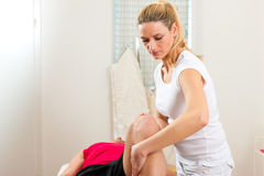 Patient at the physiotherapy. Doing physical therapy exercises with his therapist Royalty Free Stock Images
