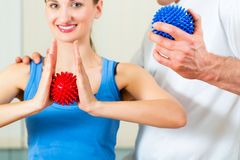Patient at the physiotherapy doing physical therapy. Female Patient at the physiotherapy doing physical exercises with her therapist, they using a massage ball Royalty Free Stock Image