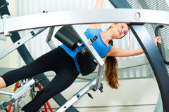 Patient at the physiotherapy doing physical therapy. Space Curl - Patient at the physiotherapy making physical exercises with special equipment Stock Photo