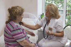 Patient plus âgé à une infirmière dans une clinique gériatrique image stock