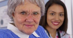 Patient plus âgé et travailleur social mexicain regardant l'appareil-photo images stock