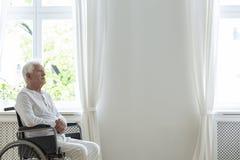 Patient plus âgé seul dans un fauteuil roulant dans une salle blanche à côté d'un mur vide Placez votre logo photos libres de droits