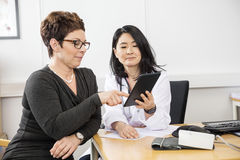 Patient Pointing At Digital Tablet Held By Doctor Royalty Free Stock Photos