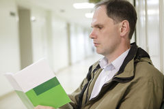 Patient in the polyclinic. Patient reading the brochure in the clinic Stock Photo