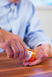 Patient pouring out RX pills into hand. Selective focus royalty free stock photography
