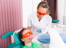 Patient at procedure of teeth whitening. Woman patient at teeth whitening procedure in the dental clinic Stock Image