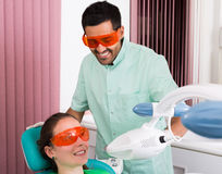 Patient at procedure of teeth whitening. Young female patient at teeth whitening procedure in the dental clinic Royalty Free Stock Photo