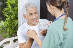 Patient Receiving Medicine And Water Glass From Female Nurse Stock Photos