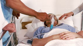 Patient receiving oxygen mask from medical team. In hospital stock video