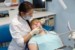 Patient at a reception  the dentist. Dentist in a private office holds reception of the patient with pain. The Dentist Selects The Tool And Starts Examination Of Royalty Free Stock Photos