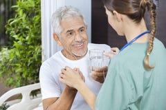 Patient recevant le verre de médecine et d'eau de l'infirmière féminine Photos stock