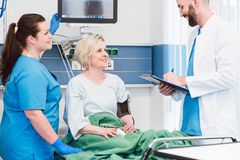 Patient in recovery room of hospital talking to doctor stock photos