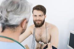 Patient regardant docteur While Undergoing Electrotherapy Photographie stock libre de droits
