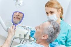 Patient regardant le miroir tandis que dentiste professionnel vérifiant des dents photos stock