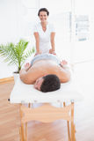 Patient relaxing on the massage table with physiotherapist behind Royalty Free Stock Photos
