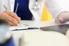 Patient remplissant de docteur de main de prise de stylo femelle d'argent photo stock