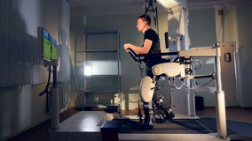 A patient during robot-assisted therapy with the Lokomat device. The Lokomat assists user`s walking movements and is used to improve mobility stock footage