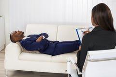 Patient s'étendant sur le divan en Front Of Psychiatrist photo stock
