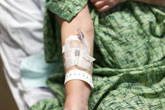 Patient's arm with IV started and hospital wrist band. A female patient wearing a green gown is resting her arm that has an IV started and she also wears a stock photo