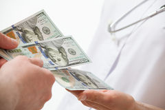 Patient's hand giving a money to doctor Royalty Free Stock Photo
