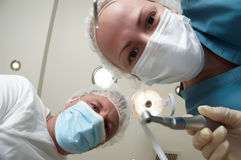 Patient's view of the dentist and assistant. Patient from the dental chair view of the dentist and assistant Stock Photography