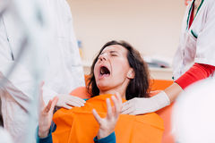 Patient screaming at the dentist. Woman screaming because of dental pain in dental office Royalty Free Stock Photography