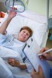 Patient se trouvant sur le lit tandis qu'écriture d'infirmière sur le presse-papiers photographie stock libre de droits