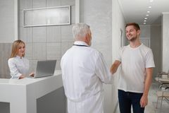 Patient shaking hands with doctor in private hospital. stock photo