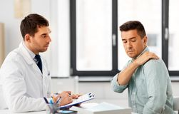 Patient showing sore shoulder to doctor at clinic. Medicine, healthcare and people concept - male patient showing sore arm to doctor at medical office in stock images