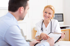 Patient signing the document of a young attractive doctor Stock Image