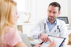 Patient signing the document of a young attractive doctor Stock Photography