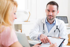 Patient signing the document of a young attractive doctor Royalty Free Stock Photo