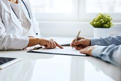 Patient signs a document with his doctor. In medical office stock photos