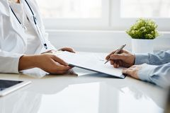 Patient signs a medical report with his doctor stock photos